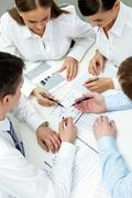 high angle view of four businesspeople working with financial data - stock photo