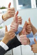 Hands of four businesspeople showing big thumbs Stock Photos