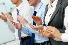 Neljä liikemiehet taputtaa seminaarissa Kuvituskuvat
