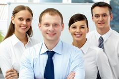 Stock Photo of portrait of four businesspeople, looking at camera and smiling