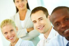 Four smiling business workers looking at camera, the focus is on young man Stock Photos