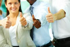 four business people showing big thumbs - stock photo