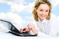 Image of pretty girl looking at camera with laptop near by Stock Photos