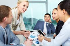 Businesswoman explaining business plan to her colleagues Stock Photos