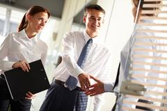 business leader handshaking with his employee with secretary near by - stock photo