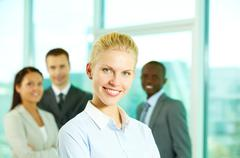 young woman looking at camera and smiling with her colleagues in the background - stock photo