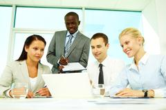 four businesspeople sitting at table, watching presentation and making notes - stock photo