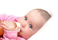 Baby drinking juice form bottle Stock Photos
