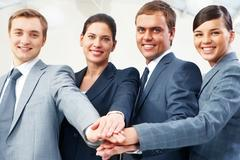row of business people keeping their hands in pile symbolizing support and power - stock photo
