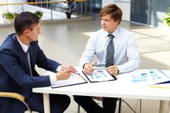 two businessmen sitting at table and discussing strategy - stock photo