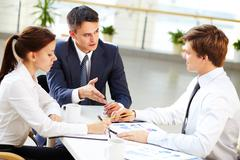 Business leader and his employees discussing the results of work Stock Photos