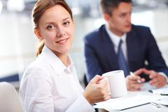 Portrait of smiling secretary with cup of coffee looking at camera during briefi Stock Photos