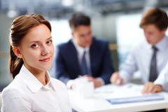 young secretary looking at camera and smiling against her colleagues - stock photo