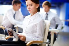 portrait of young secretary sitting in office and smiling - stock photo