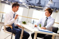 Two businessmen sitting at table and discussing strategy Stock Photos