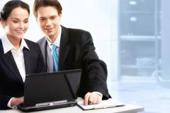 creative image of two partners working with laptop in office - stock photo