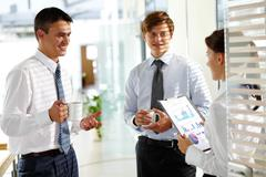 three colleagues communicating in office at break - stock photo