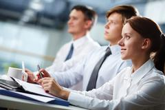 Stock Photo of three business people sitting at seminar, the focus is on woman