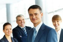 A young businessman smiling against three partners Stock Photos