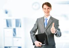 portrait of happy businessman holding the laptop and showing thumb up - stock photo
