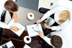 Image of company of successful partners discussing business papers at meeting Stock Photos