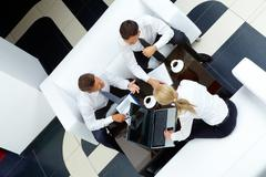 photo of successful employees discussing business plan at meeting - stock photo