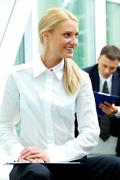 Stock Photo of confident businesswoman looking aside at background of reading man