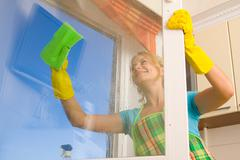 Women cleaning a window 4 Stock Photos