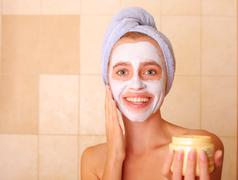 Beautiful woman puts on the face a mask Stock Photos