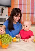 Beautiful happy mum with son eat fruit Stock Photos