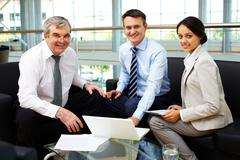 Portrait of happy team looking at camera at workplace Stock Photos
