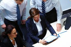 Image of confident colleagues looking at business document in office Stock Photos