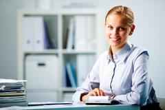 portrait of a young happy businesswoman looking at camera in office - stock photo