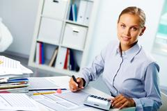 portrait of a young happy businesswoman looking at camera while working in offic - stock photo