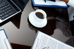 Image of porcelain cup with strong black coffee on workplace Stock Photos