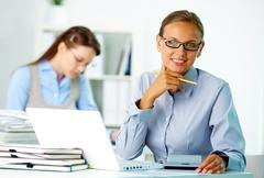Portrait of pretty businesswoman looking at camera in working environment Stock Photos