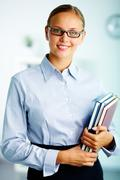 portrait of elegant businesswoman with handbooks looking at camera - stock photo