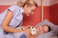 mum puts to bed a sonny 5 - stock photo
