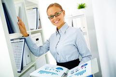 portrait of happy businesswoman looking for book on the shelf in office - stock photo