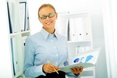 portrait of elegant businesswoman looking at camera in office - stock photo
