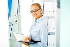 Portrait of elegant businesswoman looking at camera in office Stock Photos