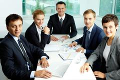 Image of confident partners gathered at workplace in office Stock Photos