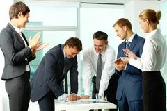 image of co-workers congratulating their colleague while he signing paper at mee - stock photo