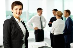 attractive businesswoman looking at camera and smiling aginst her colleagues - stock photo