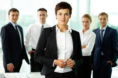 portrait of female manager against her colleagues - stock photo