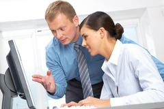 young manager explaining something at laptop to his colleague - stock photo