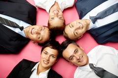 Five businesspeople lying in circle, looking at camera and smiling Stock Photos