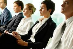 Business people sitting in a row at seminar Stock Photos