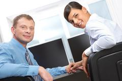 Two business colleagues looking at camera and smiling Stock Photos