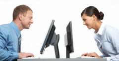 Two business colleagues sitting opposite at their monitors Stock Photos